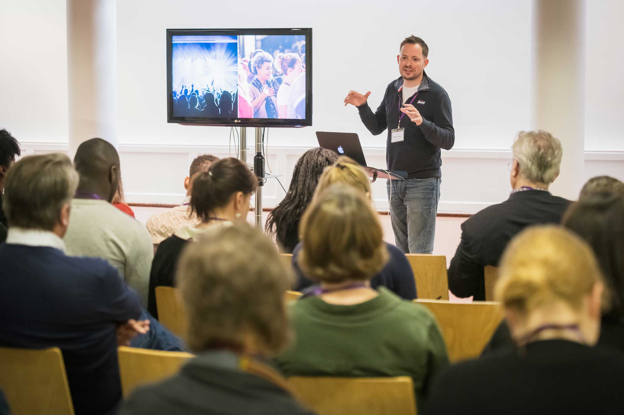 presenter gives talk with tv screen to delegates at conference at Conference with screens and sofa style seating at St Mary's Venue Hire, London