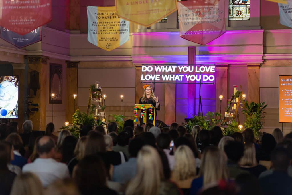 speaker on stage with coloured banners and event lighting at St Mary's Venue Hire, London