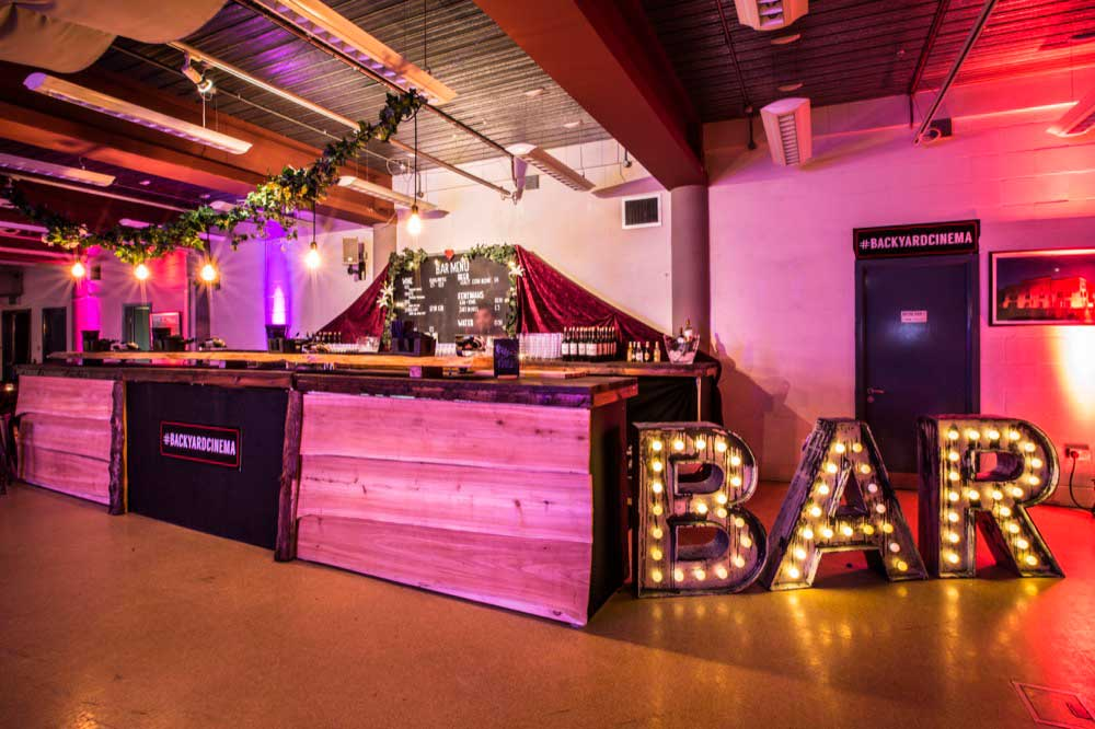 Red lighting and extended wood clad bar on the lower floor at Conference with screens and sofa style seating at St Mary's Venue Hire, London
