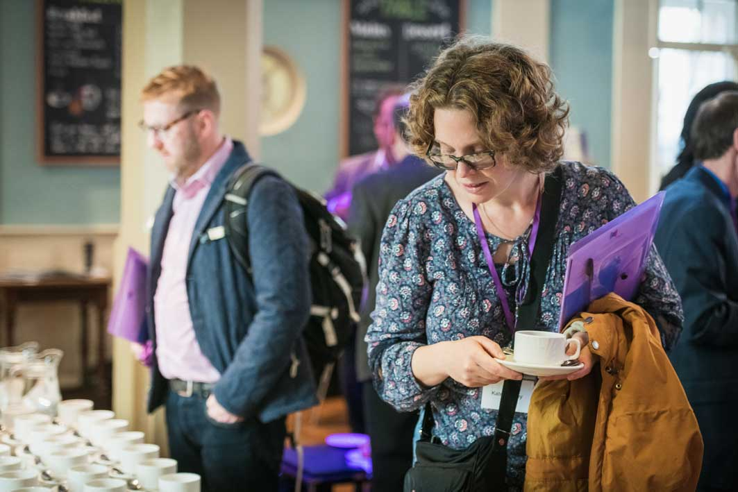 Delegates getting refreshments at conference at Conference with screens and sofa style seating at St Mary's Venue Hire, London