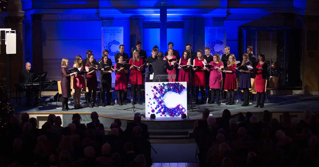 choir on stage at christmas concert at Conference with screens and sofa style seating at St Mary's Venue Hire, London