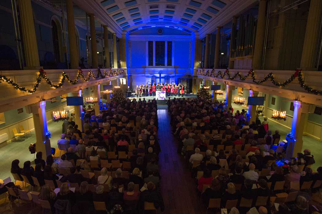 guests at carol concert with fairy lights and blue event lighting