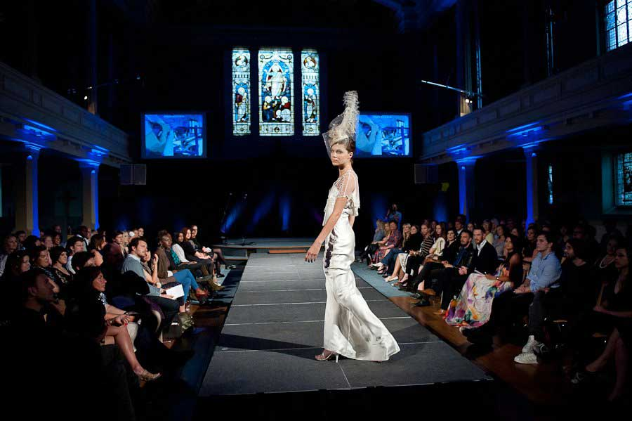Model in white outfit with blue lighting at fashion show at Conference with screens and sofa style seating at St Mary's Venue Hire, London
