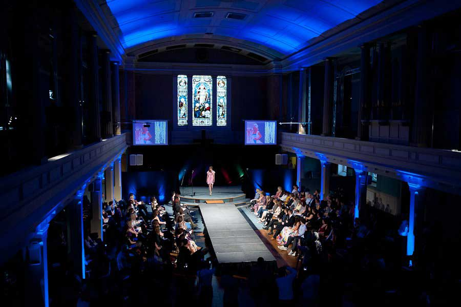 blue atmospheric event lighting and single runway at fashion show at Conference with screens and sofa style seating at St Mary's Venue Hire, London