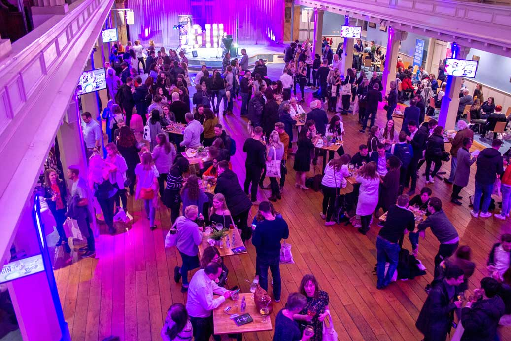 guests at poseur tables at alcohol festival with purple event lighting