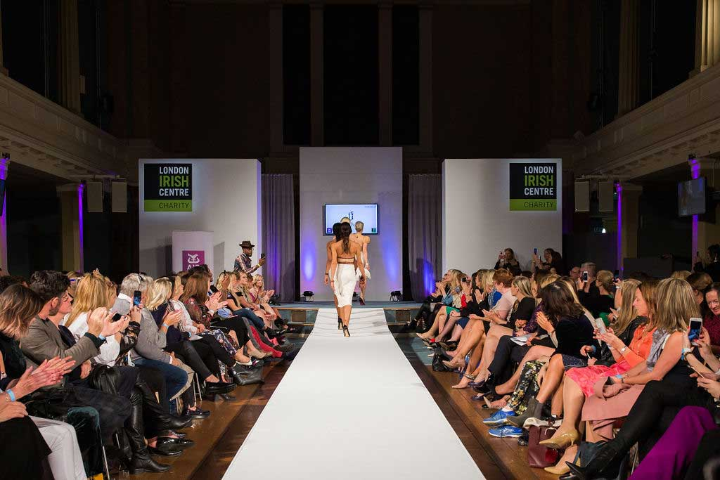 Models walking down catwalk at Conference with screens and sofa style seating at St Mary's Venue Hire, London