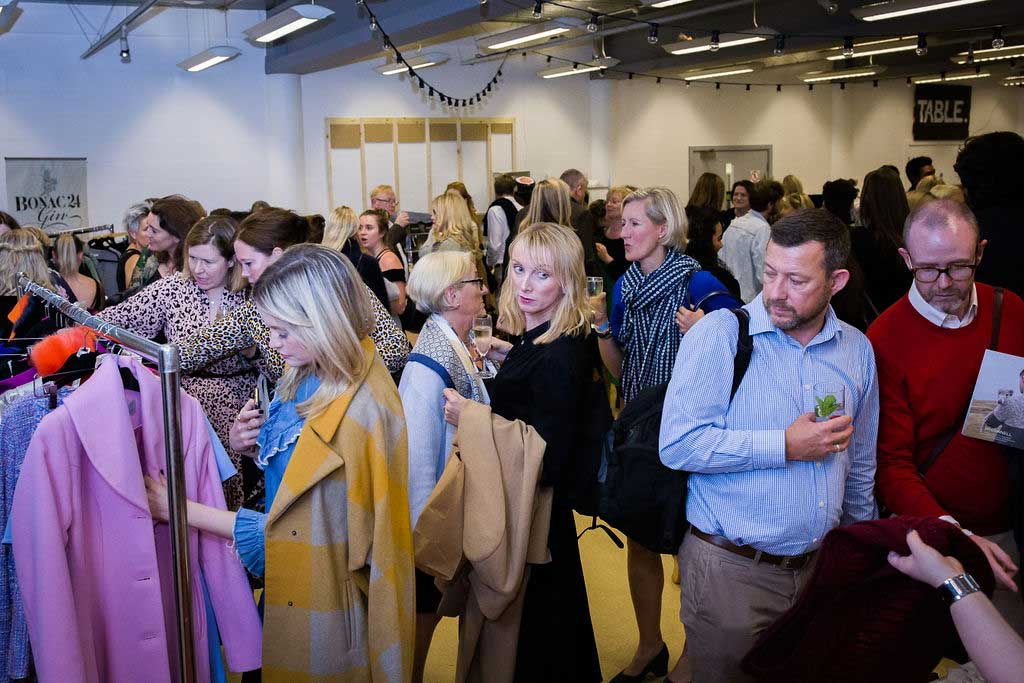 Guests shop at market stalls at a fashion show at Conference with screens and sofa style seating at St Mary's Venue Hire, London