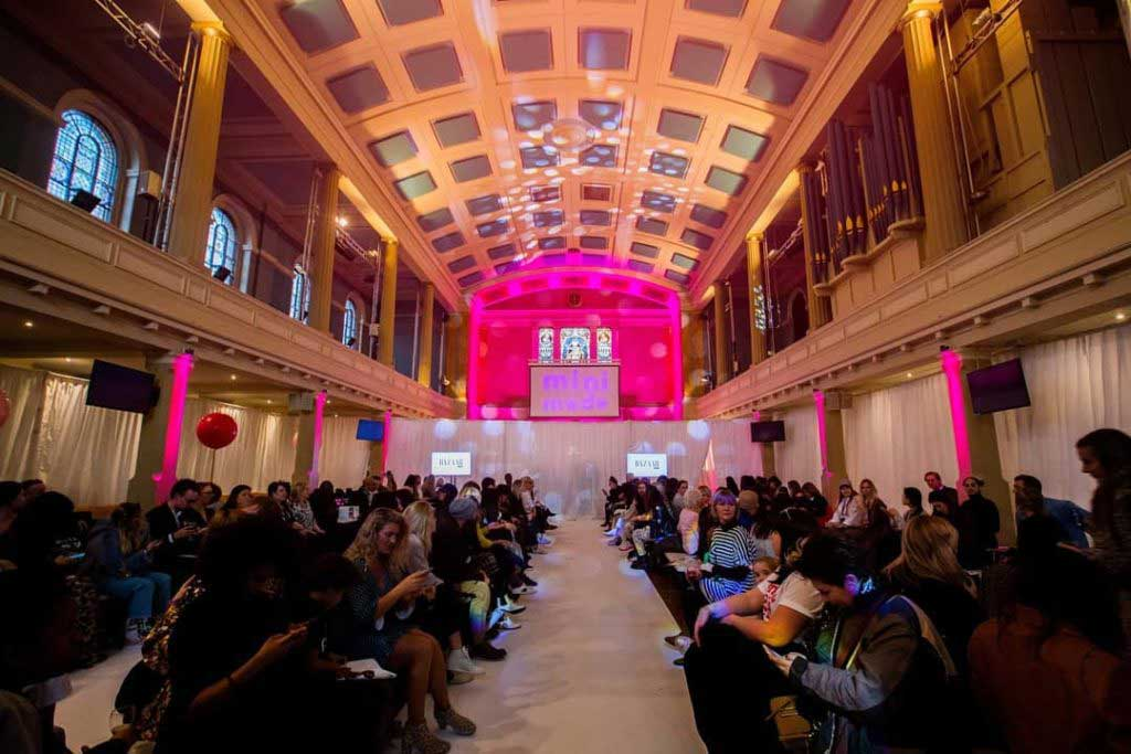 guests at mini mode fashion show with pink lighting and double catwalk