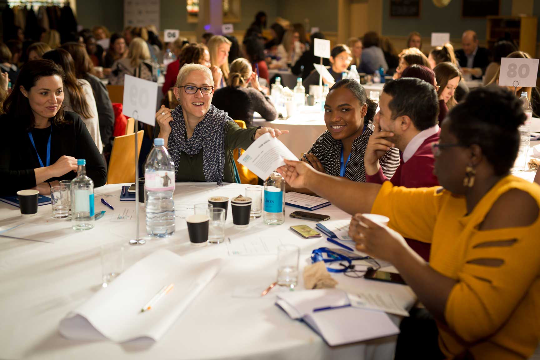 Women talking around round table at conference at Conference with screens and sofa style seating at St Mary's Venue Hire, London