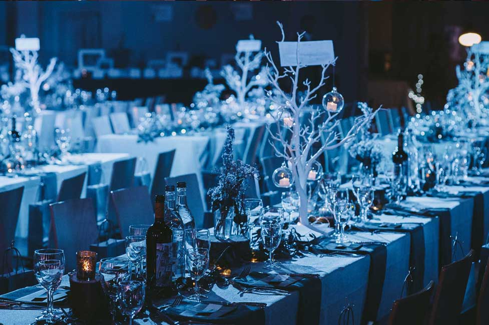 Blue atmospheric lighting and place settings of banquet style dining a St Mary's Venue Hire, London