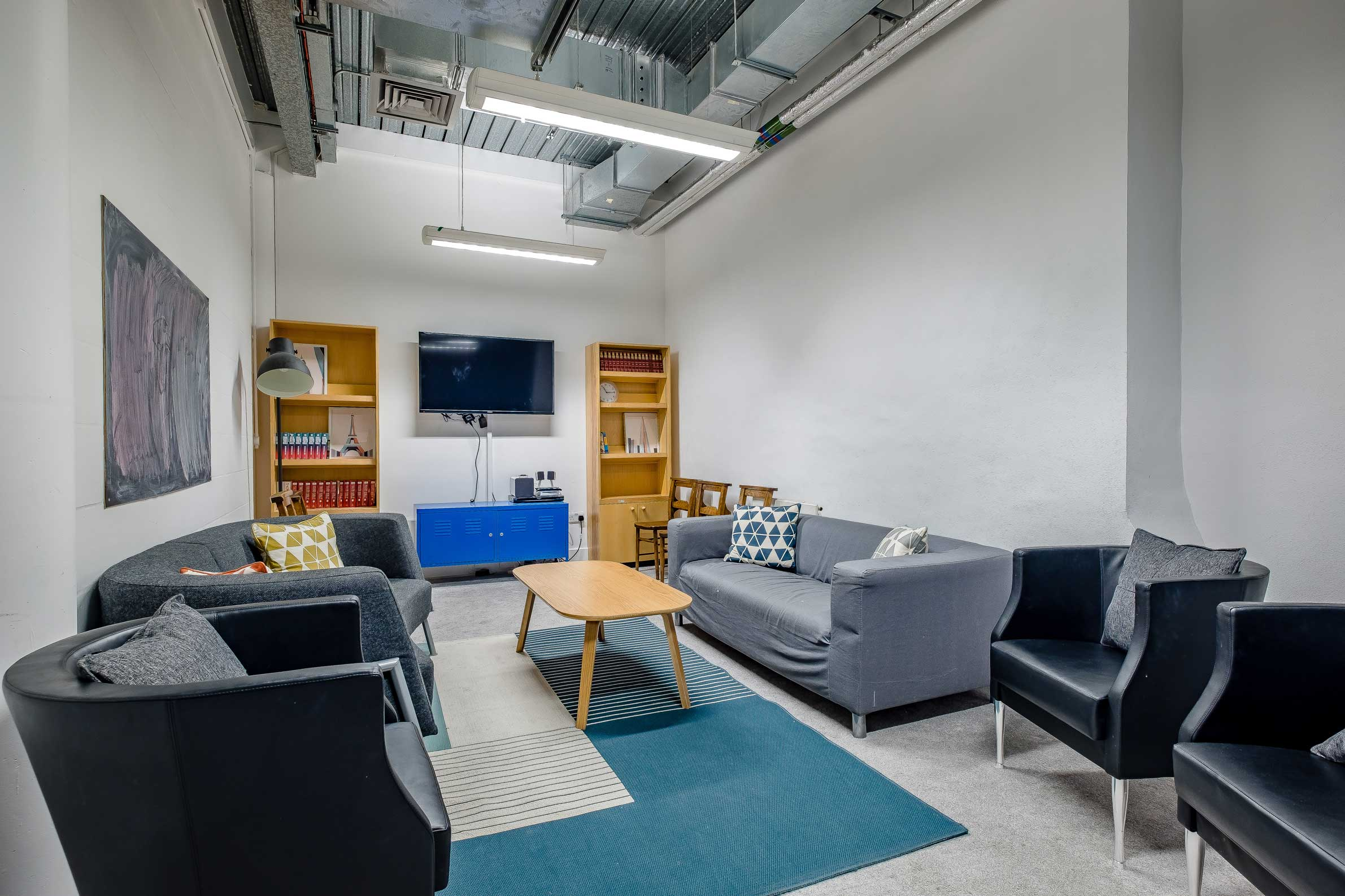 Meeting Room 2 with sofas, arm chairs, bookshelves and tv