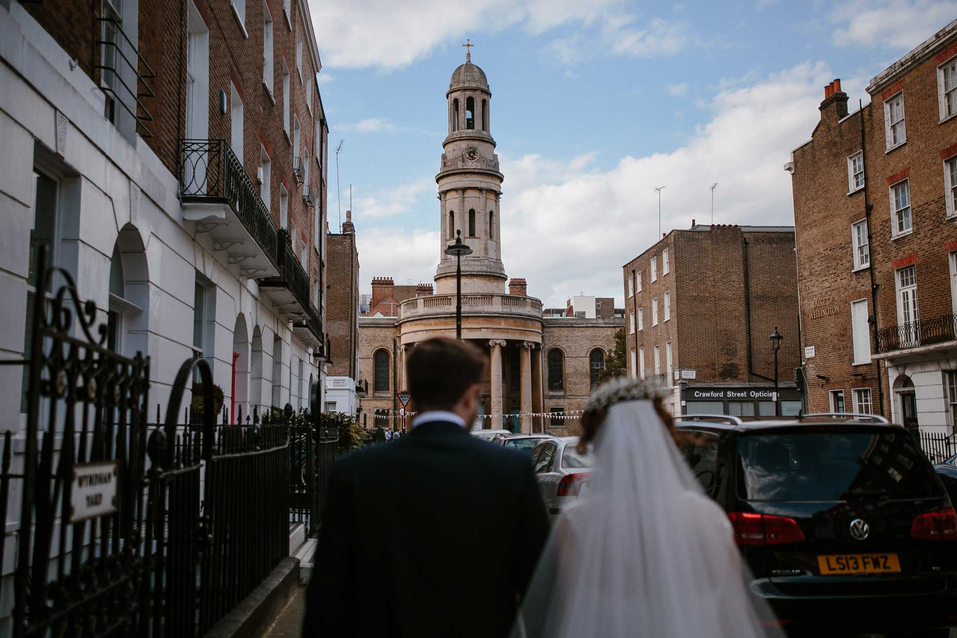 Bride and Groom walking towards the church