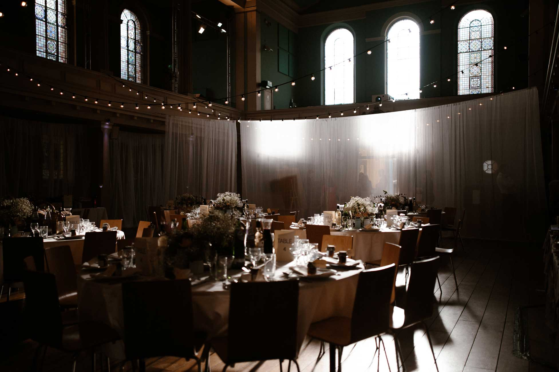 Low lit dining tables for a wedding breakfast with drapes