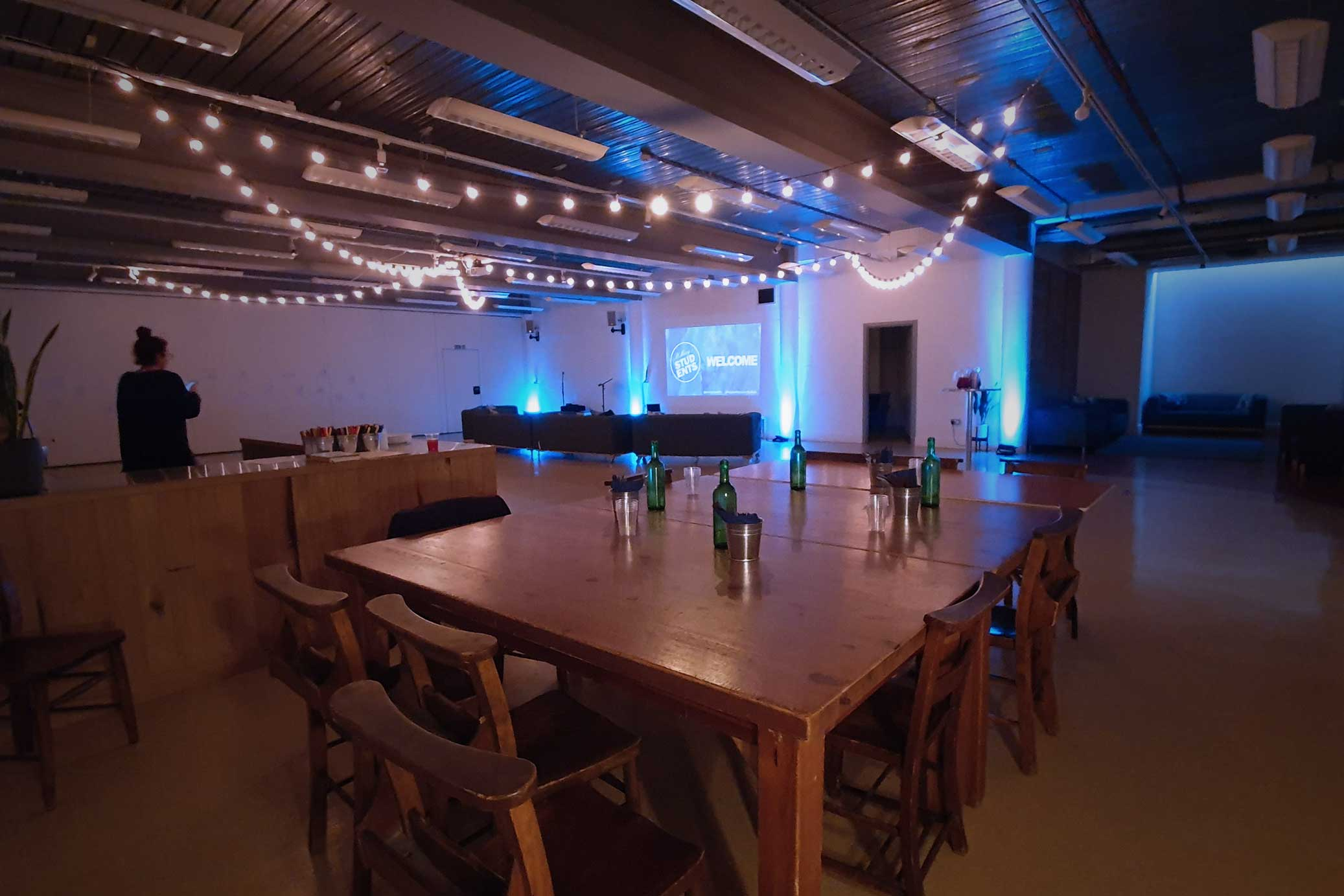 blue lighting and festoons on the lower floor at Conference with screens and sofa style seating at St Mary's Venue Hire, London