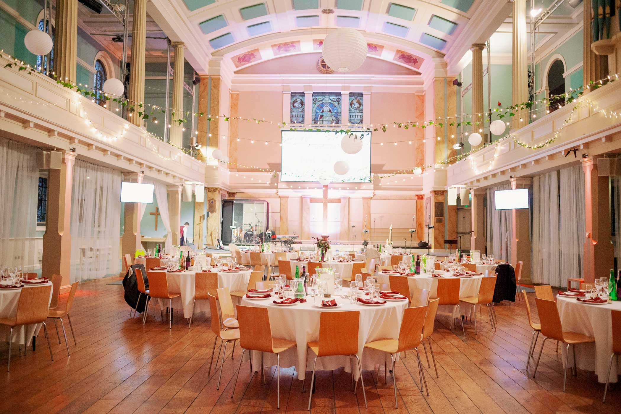 cabaret style dining at a wedding with red event lighting, fairy lights and foliage.