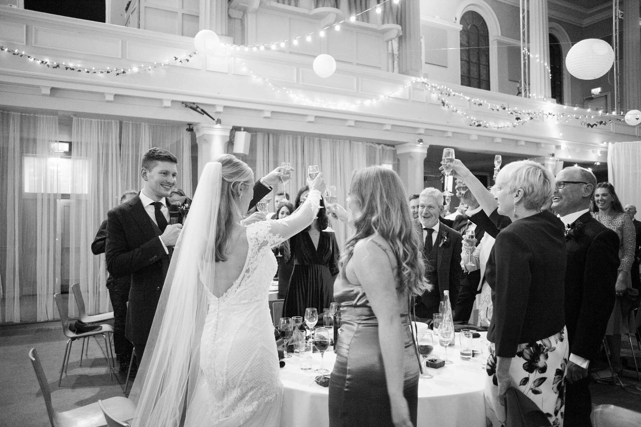 Toasting the bride and groom in black and white