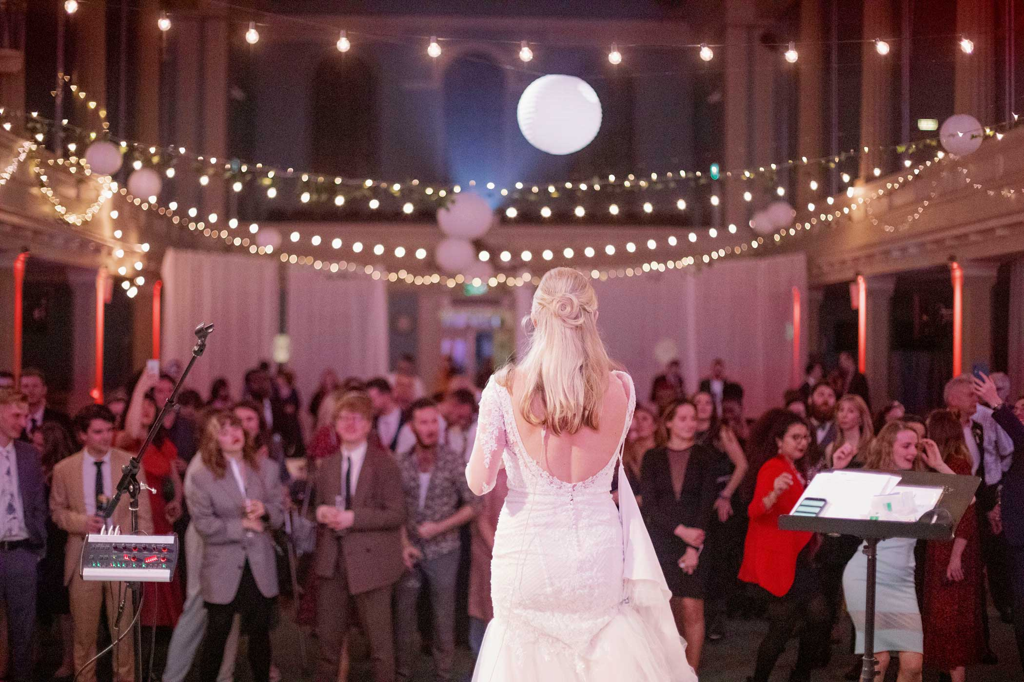 Bride singing to room of dancing guests with festoon lighting