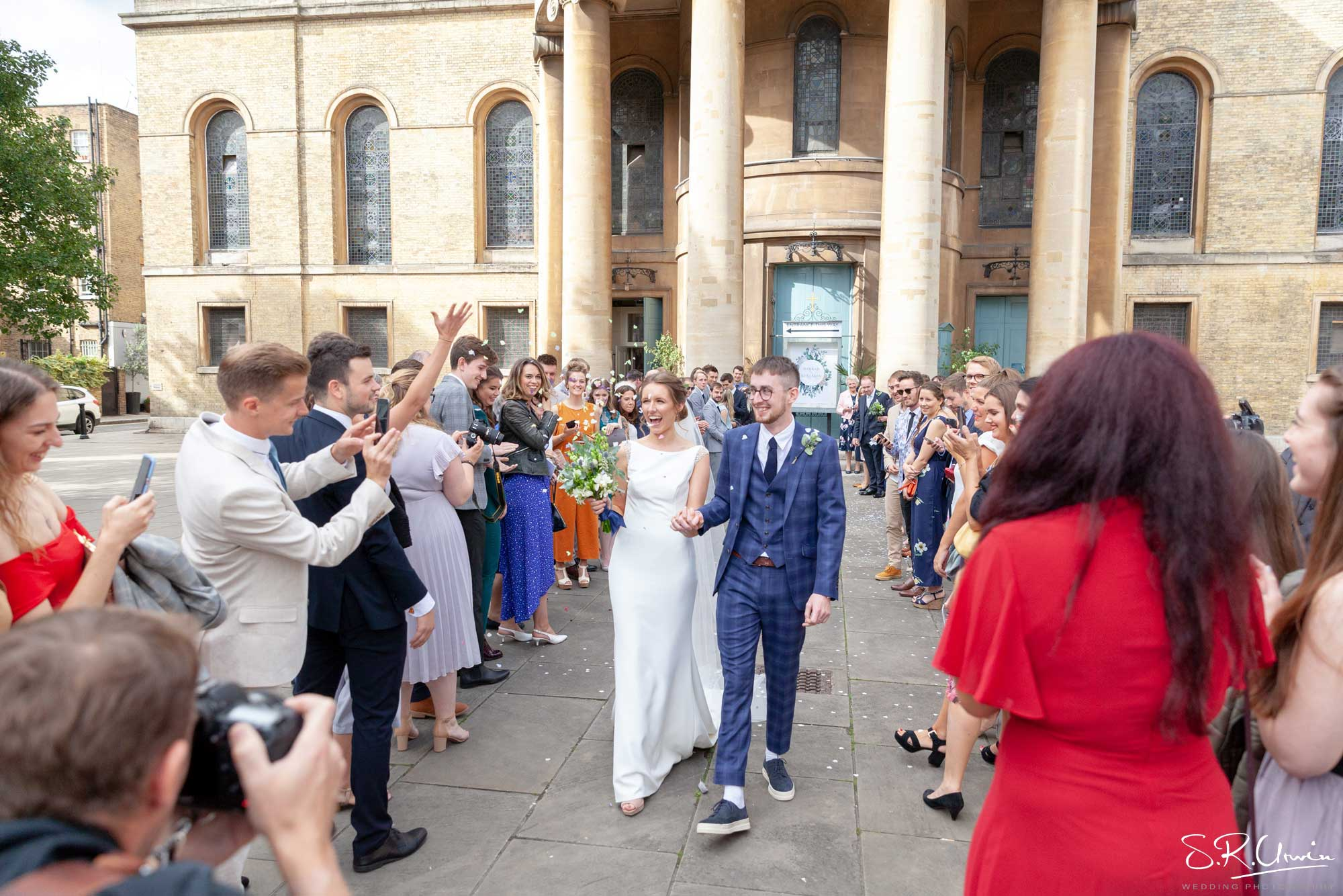 Bride and groom leaving the venue whilst guest throw confetti