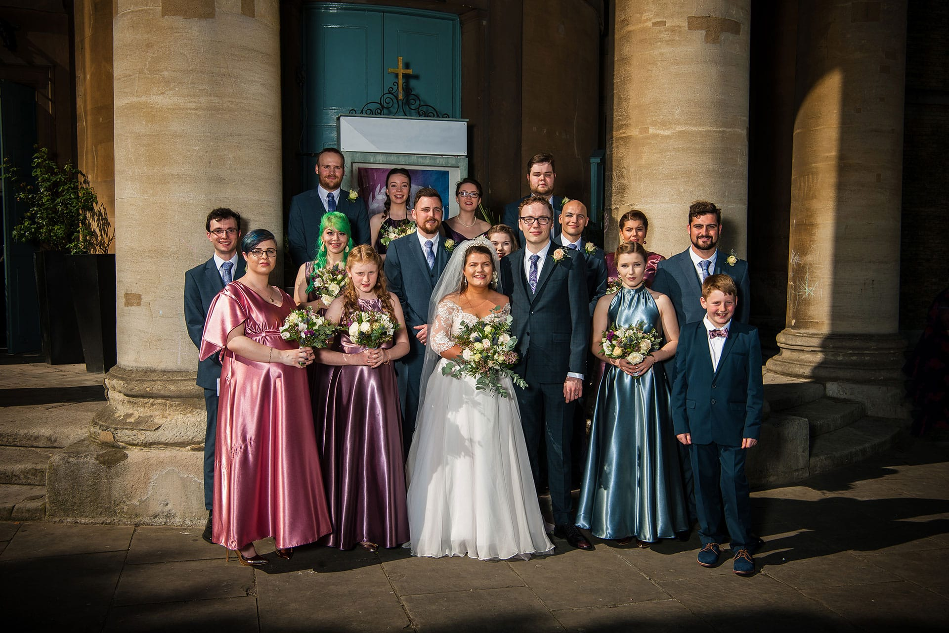 wedding party smiling as they have their photo taken outside the venue