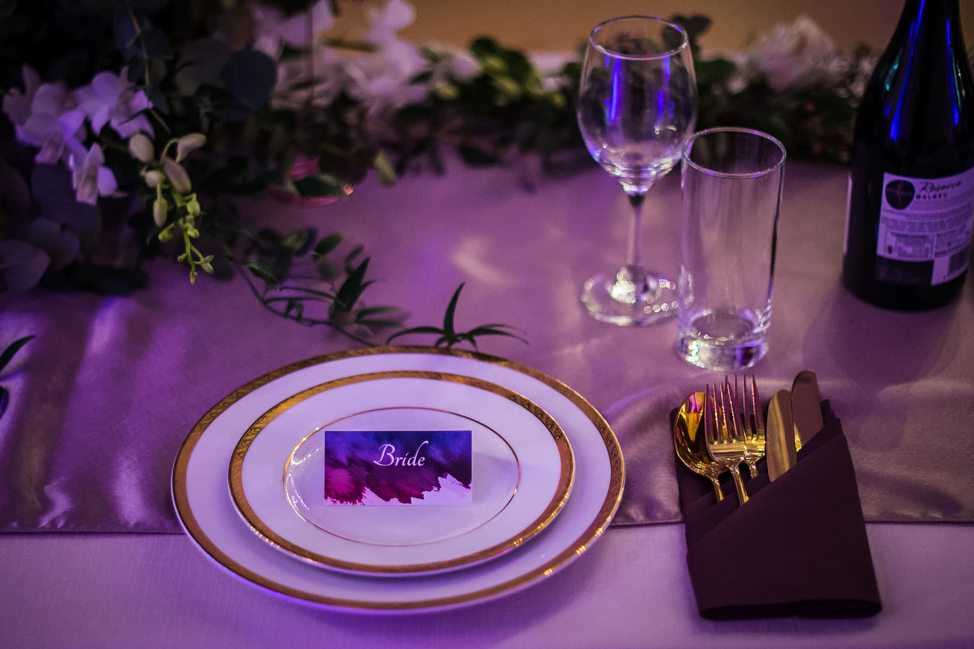 Table setting in purple, gold and champagne