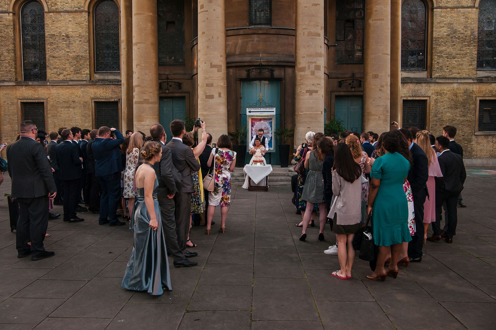 Guests watch as the couple cut the cake on the piazza outside St Mary's Venue Hire, London