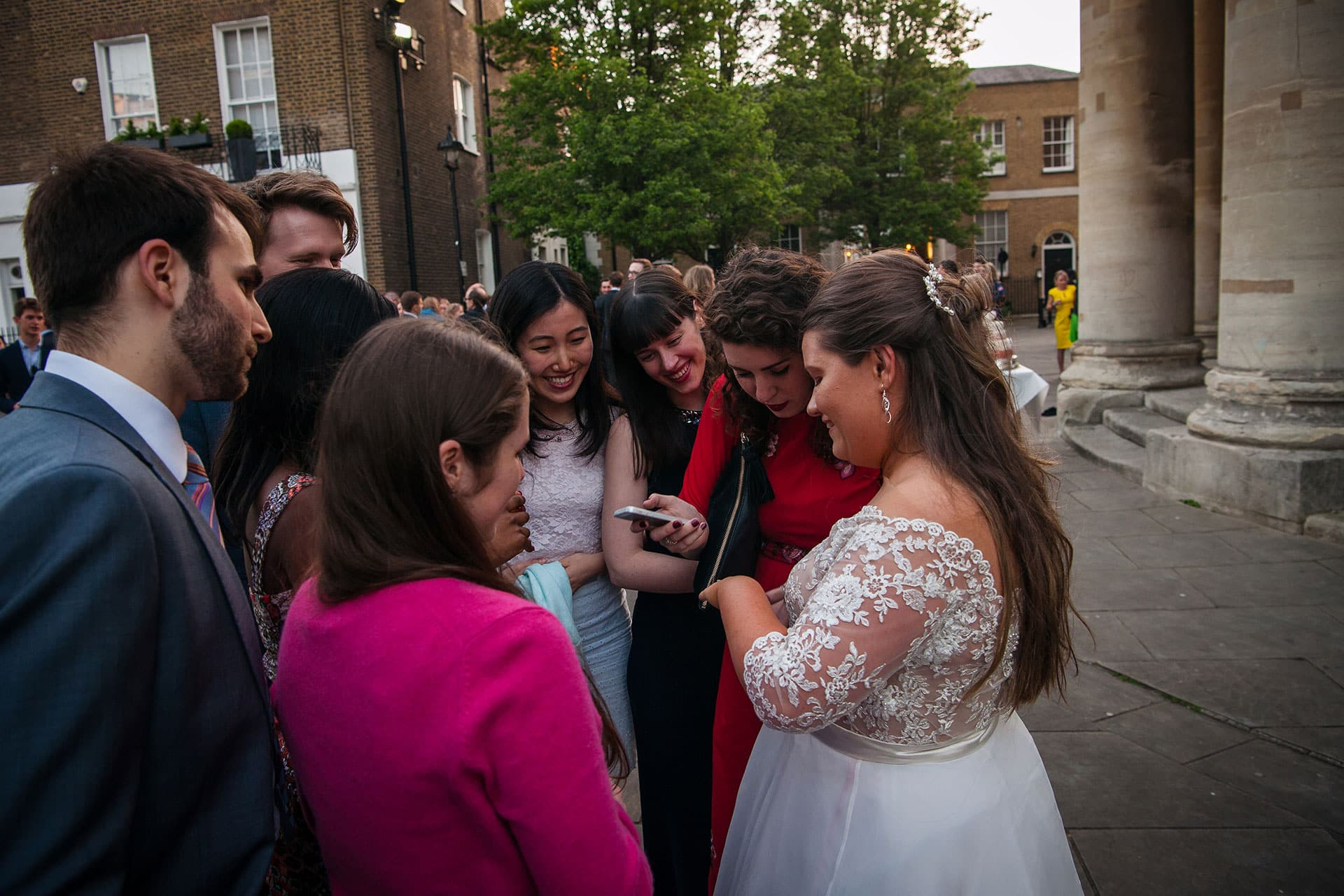 guests admire the brides wedding ring on the piazza outside