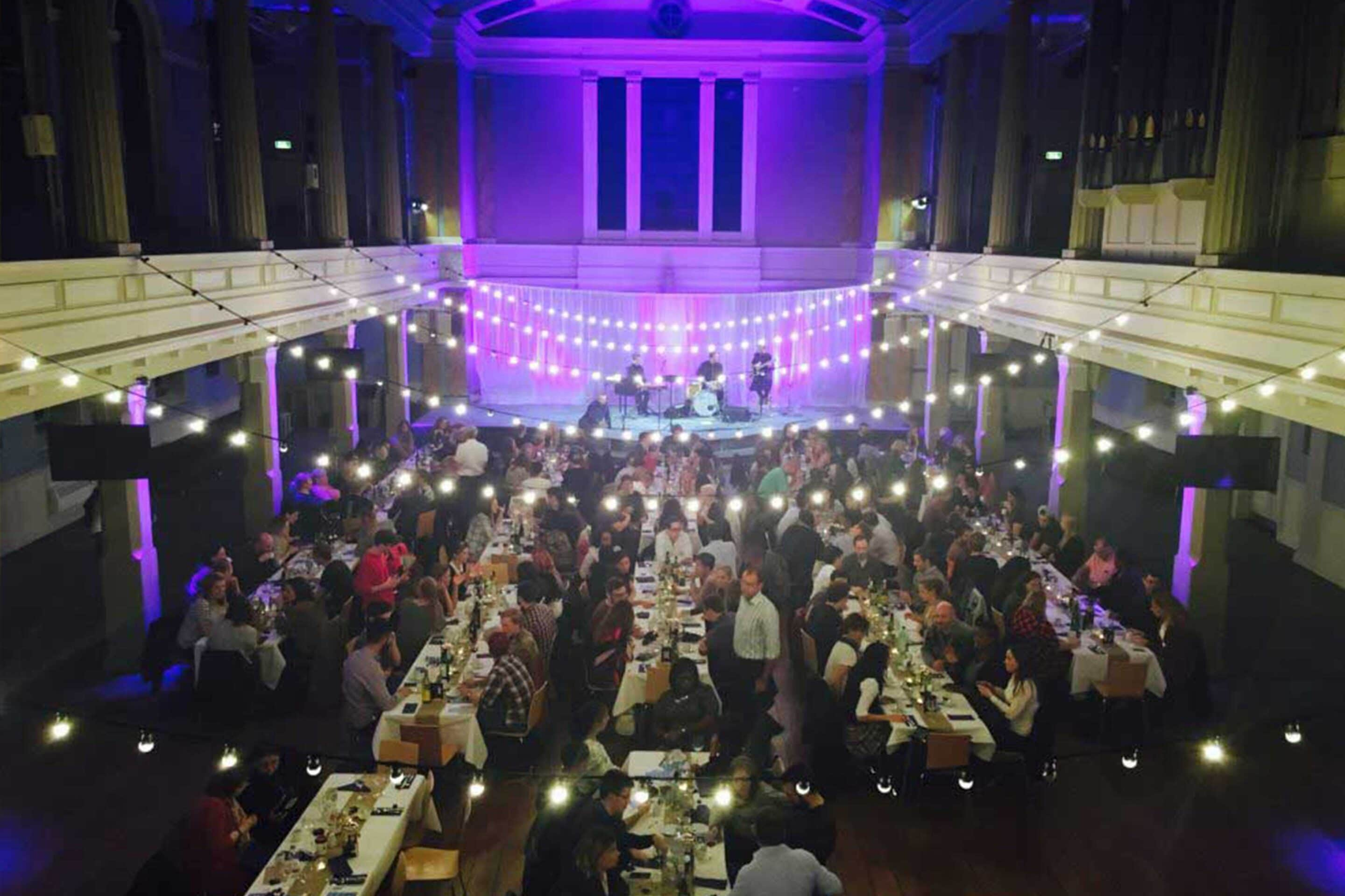 Banquet style dining with festoons and atmospheric lighting at St Mary's London Venue Hire