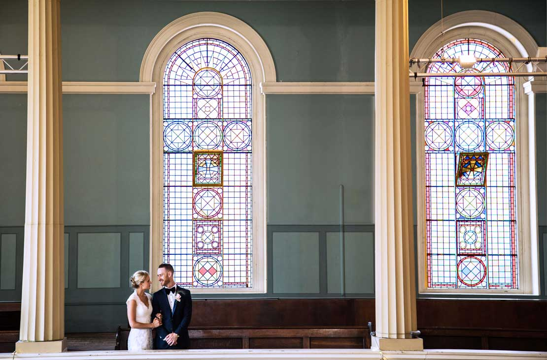 A newly married couple pose for a photograph by the stained glass windows at St Mary's Venue Hire, London