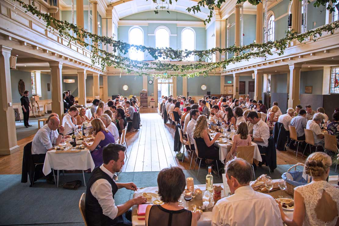 A busy dining scene at a wedding reception at St Mary's Venue, London