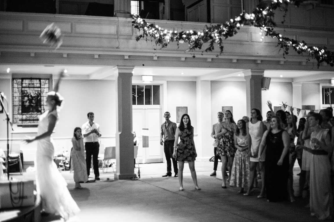 A bride throws a wedding bouquet at a wedding reception at St Mary's Venue Hire, London