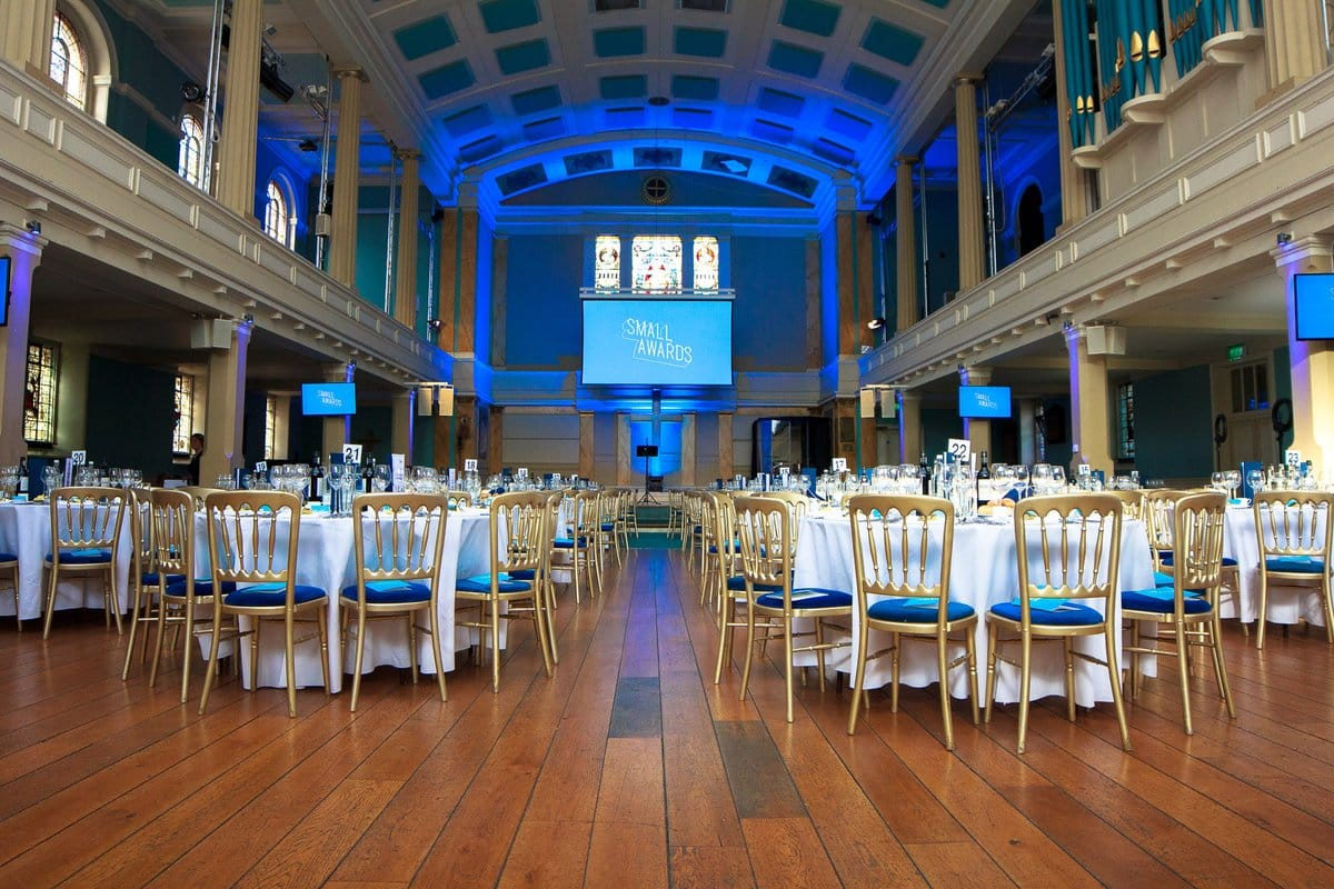 Cabaret dining with gold chairs and blue event lighting at St Mary's Venue Hire, London